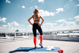 Slender sportswoman is standing with focus on back and looking forward at city. She is having training with outfit on sunny roof of urban house. Girl is using towel and smartphone while doing sport