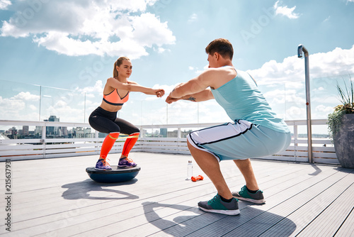 Foto Murales Strong man is doing sit-ups while girlfriend is squatting on fitness half ball and using resistance band on thighs. They are having joint work out on sunny terrace in city center under blue sky