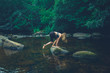 Quadro Young woman climbing a rock in the river
