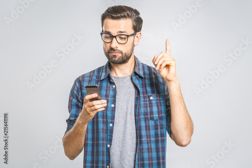 Idea! Young stylish hipster guy dressed in shirt, holds smart phone, reads something attentively, raises index finger, quotes someone words, proves his rightness. People and technology concept