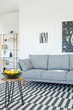 Grey sofa and table on patterned carpet in bright living room interior with posters. Real photo - 215643164