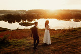 Romantic landscape, newlywed couple posing at sunset field near a lake, handsome groom walking towards gorgeous bride - 215643134