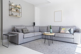 Grey corner sofa and wooden table in spacious living room interior with posters and carpet. Real photo