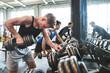 Leinwandbild Motiv Young fit men in gym exercising with dumbbells.