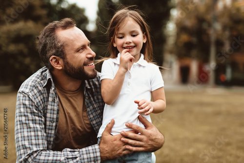Leinwandbild Motiv Side view of delighted man squatting near small kid and holding her. Little girl is standing with smile and enjoying leisure outdoors