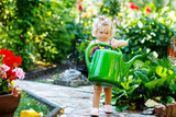 Cute little baby girl in colorful swimsuit watering plants and blossoming flowers in domestic garden on hot summer day. Adorable toddler child having fun with playing with water and can