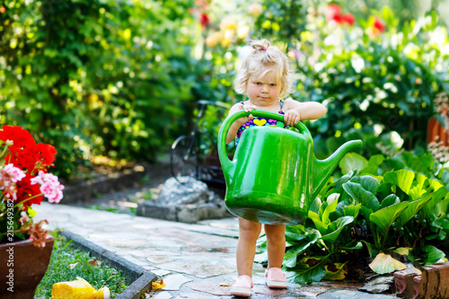 Leinwandbild Motiv Cute little baby girl in colorful swimsuit watering plants and blossoming flowers in domestic garden on hot summer day. Adorable toddler child having fun with playing with water and can