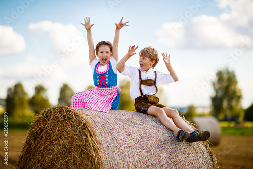 Leinwandbild Motiv Two kids, boy and girl in traditional Bavarian costumes in wheat field with hay bales