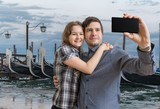 Young couple is taking selfie with smartphone in Venice in Italy.