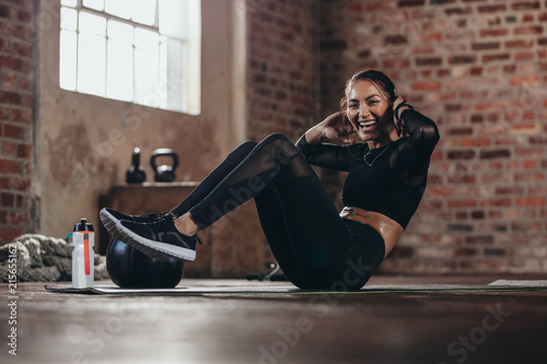 Smiling female in the gym doing sit-up