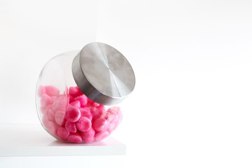 Soft pink candy in a glass jar on a white shelf
