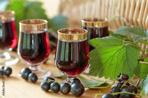 Homemade black currant liqueur and fresh berries. - 215676115
