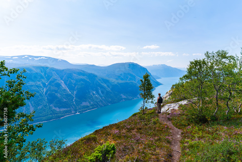 Foto Spatwand Blauwe hemel Man watching over the fjord in Norway, near Seimsdalen. Name of the fjord is Lurefjorden