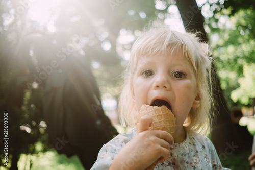 Foto Murales Adorable little girl eating ice cream in the park
