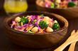 Frischer Salat aus Rotkohl, Kichererbsen, Karotten und Broccoli serviert in Holzschüsseln, fotografiert mit natürlichem Licht (Selektiver Fokus, Fokus in die Mitte des Bildes)