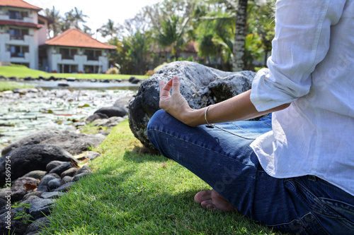Fototapeta Young woman meditating of doing yoga in nature near beautiful lotus lake