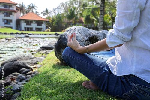 Obraz na płótnie Young woman meditating of doing yoga in nature near beautiful lotus lake