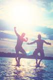 Glückliche junge Menschen laufen und springen am See beim Sonnenuntergang - 215695924