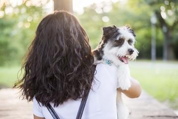 brunette girl from behind holding her dog © Djordje
