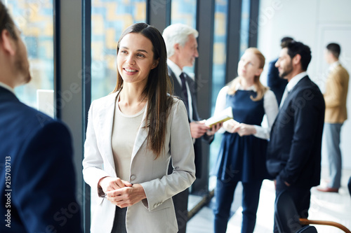 Leinwandbild Motiv Smiling pretty young business lady in jacket talking to colleague and discussing business forum topics during break