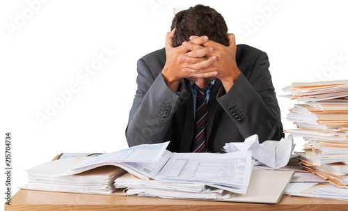 Leinwandbild Motiv Businessman near heap of papers on background