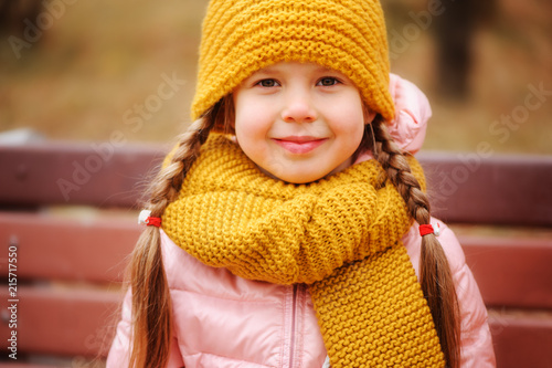 autumn outdoor portrait of happy little child girl enjoying the walk in sunny park in warm knitted hat and scarf