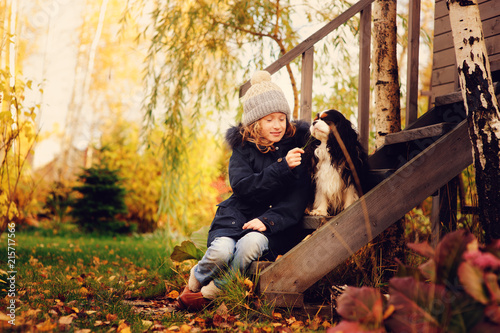 Leinwanddruck Bild autumn portrait of happy kid girl playing with her spaniel dog in the garden, sitting on wooden stairs and hugs