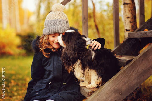 Leinwanddruck Bild - mashiki : autumn portrait of happy kid girl playing with her spaniel dog in the garden, sitting on wooden stairs and hugs