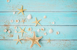 summer seashells and sand on blue wooden background - 215717977