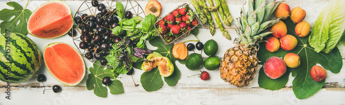 Summer food background. Flat-lay of seasonal fruit, vegetables and greens over white wooden background, top view. Vegetarian, vegan, dieting, clean eating, weight loss ingredients