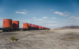 Freight cargo in large red shipping container cylinders being transported via train through the desert of Bolivia