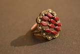 golden metal ring with red stones in it