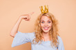 Leinwandbild Motiv Portrait of young attractive charming nice cute caucasian curly-haired blonde girl wearing golden crown and blue dress, pointing to diadem, toothy smile. Isolated over beige background