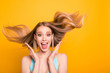 Leinwandbild Motiv Portrait of cute straight-haired blonde caucasian smiling girl, wearing casual blue shirt, amazed, showing excitement, wind blows hair. Isolated over yellow background