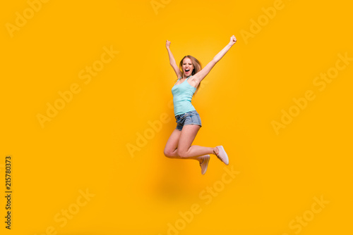 Leinwanddruck Bild Full-legh portrait of cute blondy girl happily jump and rejoices of victory rise up fists isolated on bright yellow background with copy space for text