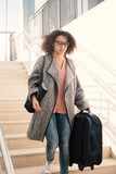 Black woman holding luggage ready for travel