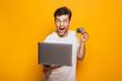 Leinwandbild Motiv Portrait of an excited young man holding laptop computer