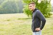 Junger Mann steht skeptisch im Freien - 215799908