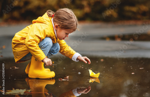 Leinwanddruck Bild happy child girl with umbrella and paper boat in   puddle in   autumn on nature.