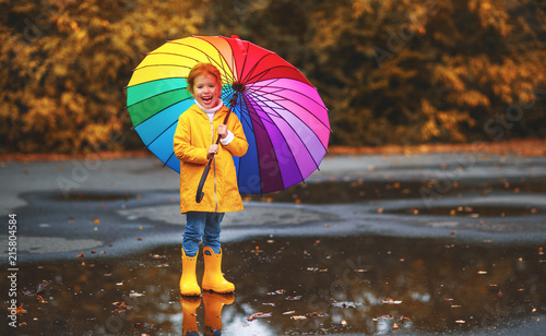 Leinwandbild Motiv  happy child girl with an umbrella and rubber boots in puddle  on autumn walk