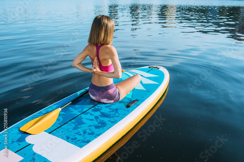 Fototapeta Young woman practicing yoga on a paddleboard In city bay, view from above , active summer rest