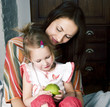Quadro mother with daughter together in bed smiling, happy family close