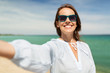 Leinwandbild Motiv summer holidays and leisure concept - happy smiling woman in sunglasses taking selfie on beach