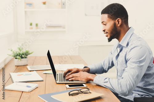 Leinwanddruck Bild Young black businessman working with laptop