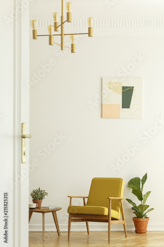 Foto Murales Comfortable yellow chair with a wooden frame in a tall and spacious living room interior with a poster on the white wall. Real photo.l