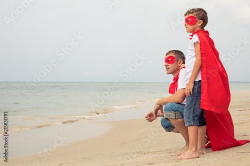 Leinwandbild Motiv Father and son playing superhero on the beach at the day time.