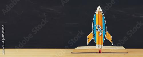 Fototapeta Back to school banner. rocket sketch and pencils over open book in front of classroom blackboard.