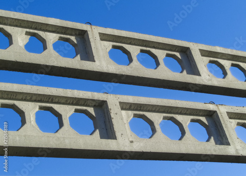 Detailed background of concrete structures. Concrete structures on the background of blue sky. Concrete beams - 215848189