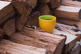 Yellow Cup of Hot Black Tea Standing on the Stacks of Firewood. Focus on Mug. - 215866926