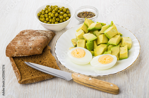 Pieces of avocado, eggs, bread, green peas, condiment, kitchen knife © Evgeny